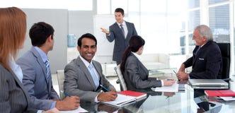 Figure di vendite di segnalazione dell'uomo d'affari alla sua squadra Fotografia Stock Libera da Diritti