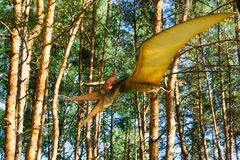 The figure of a dinosaur hovering under the trees in the forest. stock image