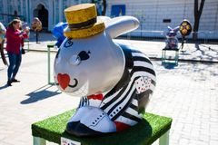 Figure of Easter bunny in a striped jacket with playing cards in his pocket and his glasses on the eyes. Beautiful Easter art deco stock photography