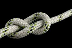 Figure-eight knot. Tied on a gray rope on black background Stock Photos