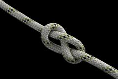 Figure-eight knot. Tied on a gray rope on black background Stock Photo
