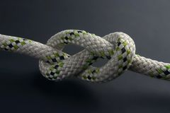 Figure-eight knot. Tied on a gray rope on black background, back-lighted Royalty Free Stock Photos
