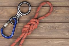 Figure eight knot with climbing carabiner and rappel eight on wooden background. Stock Photos
