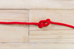 Figure-eight knot made with red rope on wooden background Stock Images