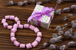 The figure-eight lined with pink marshmallow green gift box with purple ribbon spring branches with buds on a wooden brown backgro Stock Photo