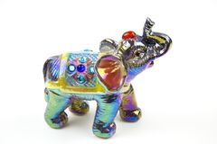 The figure of an elephant made of ceramics is decorated with colored mother-of-pearl paints turquoise purple silver Inserts of col stock photos