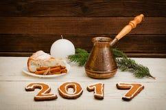 Figure em 2017 do pão-de-espécie, do ramo spruce, dos potenciômetros da vela e da torta de maçã em uma tabela de madeira Fotografia de Stock
