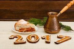 Figure em 2017 do pão-de-espécie, dos potenciômetros, do ramo spruce e da torta de maçã em uma tabela de madeira Imagem de Stock