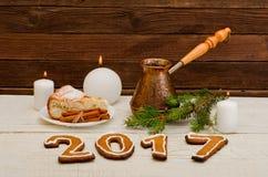 Figure en 2017 del pan de jengibre, de velas, de la empanada de manzana, de potes y de ramitas spruce en un fondo de madera Foto de archivo