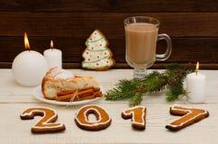 Figure en 2017 del pan de jengibre, de velas, de la empanada de manzana, de potes y de ramitas spruce en un fondo de madera Foto de archivo libre de regalías