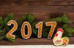 Figure en 2017 del pan de jengibre, del gallo pintado pan de jengibre, de la rama del abeto y de paredes de madera Fotografía de archivo libre de regalías