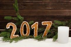 Figure en 2017 del pan de jengibre en el fondo de las ramas spruce y de las paredes de madera, vela blanca Foto de archivo libre de regalías