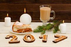 Figure en 2017 du pain d'épice, des bougies, de la tarte aux pommes, des pots et des brindilles impeccables sur un fond en bois Image stock