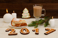 Figure en 2017 du pain d'épice, des bougies, de la tarte aux pommes, des pots et des brindilles impeccables sur un fond en bois Photo libre de droits