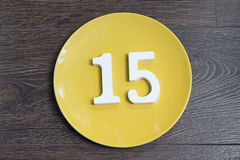 Figure fifteen on the yellow plate. Figure fifteen on the yellow plate and brown background Royalty Free Stock Images