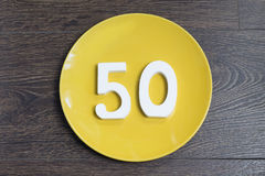 Figure fifty for the yellow plate. Figure fifty for the yellow plate and brown background Royalty Free Stock Photo