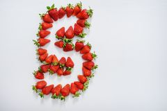The figure five is laid out with fresh strawberries, on a white wooden table stock photos