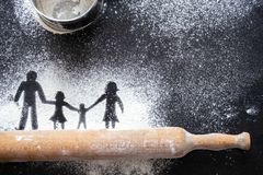Figure flour in the form of family figures on a black table. Cooking pizza. The concept of family leisure stock photos