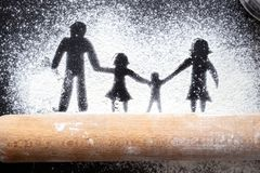 Figure flour in the form of family figures on a black table. Cooking pizza. The concept of family leisure stock images