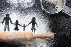 Figure flour in the form of family figures on a black table. Cooking pizza. The concept of family leisure royalty free stock image