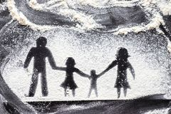 Figure flour in the form of family figures on a black table. Cooking pizza. The concept of family leisure royalty free stock photography
