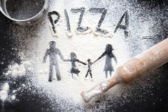 Figure flour in the form of family figures on a black table. Cooking pizza. The concept of family leisure stock photo