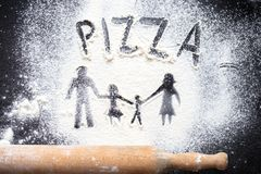 Figure flour in the form of family figures on a black table. Cooking pizza. The concept of family leisure royalty free stock photos