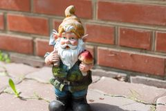 The figure of a garden gnome against a red brick wall. Close-up. Copy space.  royalty free stock photography