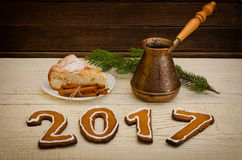 Figure in 2017 of gingerbread, candles, apple pie, pots and spruce twigs on a wooden background Stock Images
