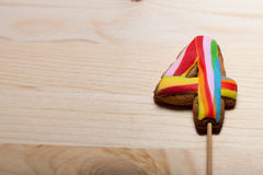 Figure of the gingerbread cookie with colored mastic on stick on. The old wooden cutting board stock photos