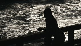 Figure of a girl on a background of the river flow stock footage