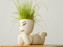 Figure with grass on his head. Lying on his stomach porcelain man with grass on his head Royalty Free Stock Image