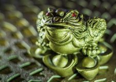 Figure of a green frog with red eyes. On brown texture Royalty Free Stock Photography