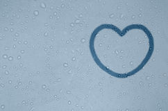 Figure of heart on a foggy blue window. Shape of heart is drawed on a fogged window glass with drops Royalty Free Stock Photography