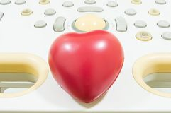 Figure heart is located on the remote control or keyboard of ultrasound machine. Concept photo for ultrasound cardiodiagnostics or Stock Photos