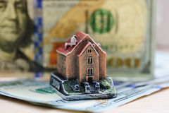 Figure at home on a background of hundred dollar bills. Concept Stock Photos