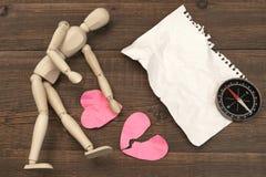 Figure humanitaire en bois, page de papier déchirée et coeurs brisés Images libres de droits