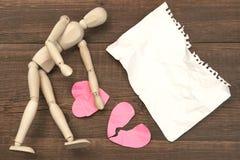 Figure humanitaire en bois, page de papier déchirée et coeurs brisés Image stock