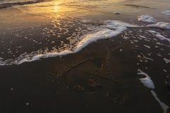 Figure le coeur percé par une flèche dessinée sur la plage sablonneuse Photo libre de droits