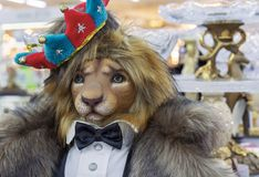 The figure of a lion is dressed in a fur coat, a tail coat with a butterfly and a crown on his head stock photo