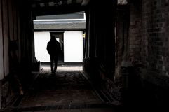 Figure of a man in an alley in the shadows royalty free stock image