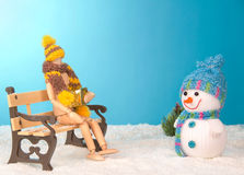 The figure of man on bench opposite snowman Stock Photo