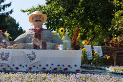 Figure of a man made of flowers seated at a table Royalty Free Stock Image