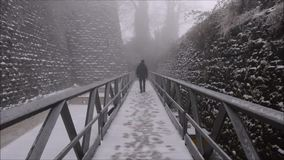 The figure of a man moving away on the bridge with snow, cold winter landscape stock video footage