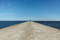 Figure of a man walking on a pier in Nida, Lithuania royalty free stock photo