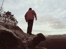 The figure of the men in red jacket on sharp cliff. Mountains within early fall daybreak Stock Image