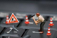 Figure miniatura che lavorano ad una tastiera di calcolatore. immagine stock libera da diritti