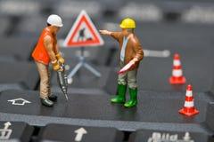 Figure miniatura che lavorano ad una tastiera di calcolatore. fotografie stock libere da diritti