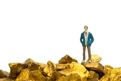 Figure miniature businessman or small people with pile of gold nuggets or gold ore on white background, precious stone or lump of. Golden stone, financial and royalty free stock image