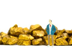 Figure miniature businessman or small people with pile of gold nuggets or gold ore on white background, precious stone or lump of. Golden stone, financial and royalty free stock photos